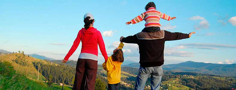 Family of four outside at the top of a grass hill looking down at a Forrest as being outside makes you happy.
