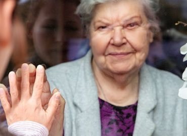 how to stay social during social distancing. Daughter seeing her mum from a glass window.