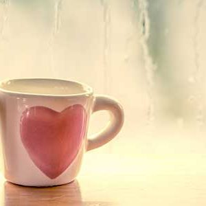 love during the coronavirus 2 heart mugs on table with rain on window in background.