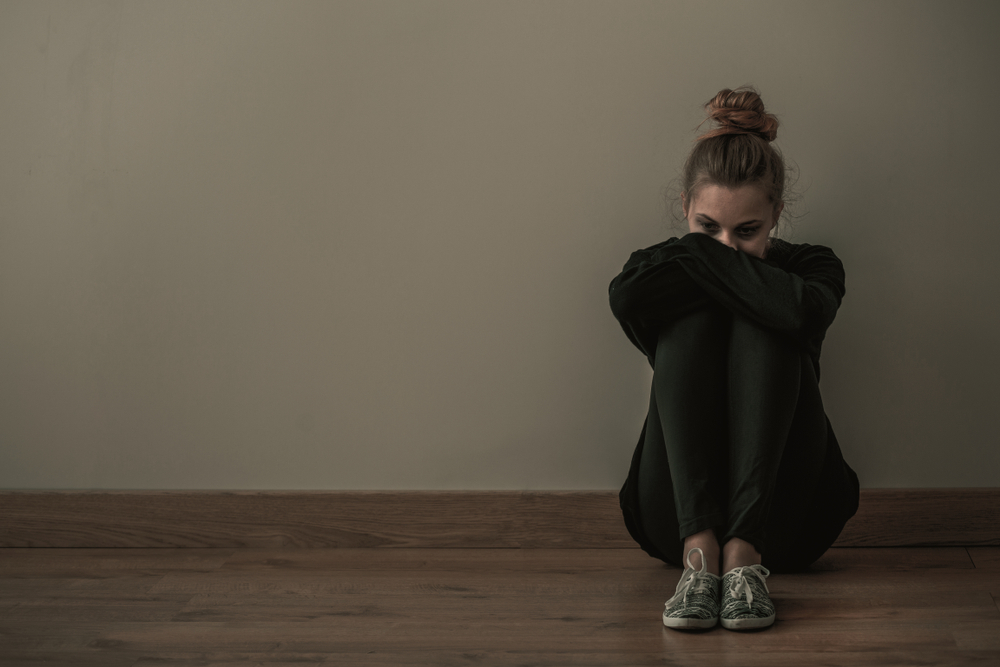 woman sitting down with signs of mental health