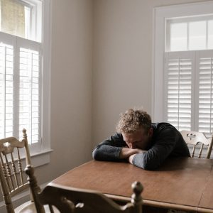 man sitting at table experiencing low mood and depression