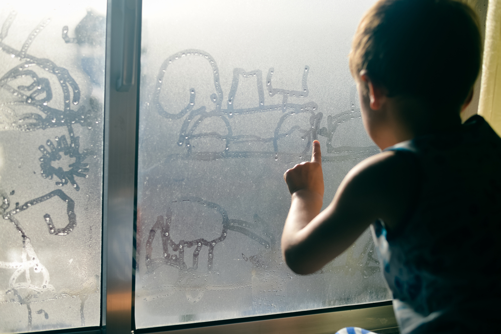 young child playing with condensation on the window