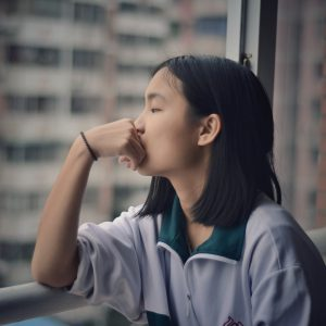 woman looking out the window with axiety