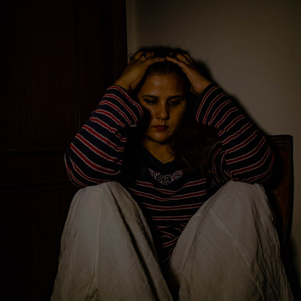 depressed woman sitting with hands on her head